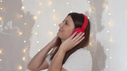 A beautiful girl in pajamas relaxes listening to music on headphones while Footage