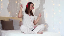A beautiful girl listens to music on headphones in red and dances using the Footage