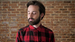 Young handsome man with beard is watching at camera, brick background Footage