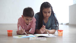 Little boy and little girl paint with paint on album lying on the floor Footage