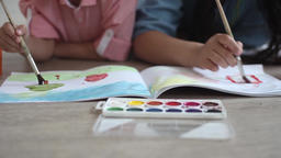 A little boy and a little girl paint with paint on the album lying on the floor Footage
