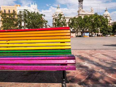 bench in a park painted in the colors of the rainbow flag in Valencia, Spain フォト