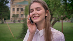 Young cute girl is talking on phone in park in summer, laughing, communication Footage