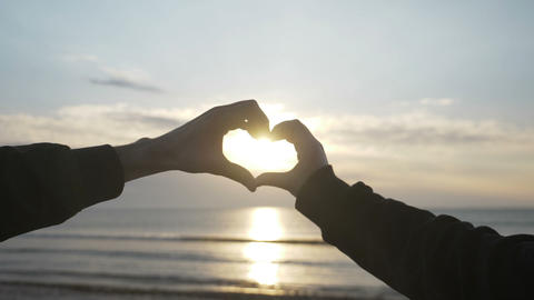 Close up of two lover hands making a heart shape while enjoying sunset and then Live Action