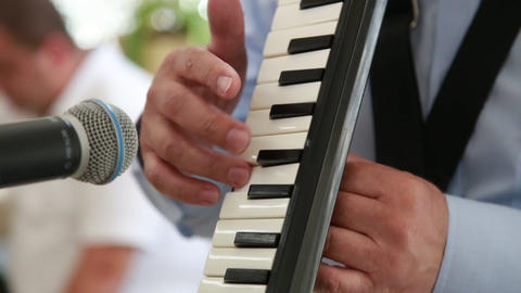Close-up of a man playing on the musical instrument MELODICA Live Action