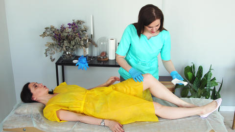Prepare the feet with cream before epilation of the legs. Close - up of the Live Action