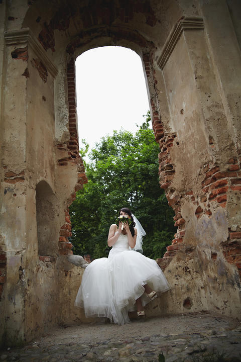 The bride is sitting on the ruins and holding a wedding bouquet Photo
