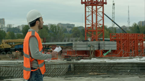 Portrait of amale site contractor engineer with helmet holding blueprint pape Footage