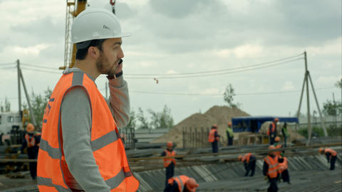 Construction worker talking on the phone at a building site Footage