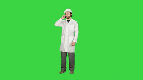 Engineer talking on the phone on a construction site on a Green Screen, Chroma Footage