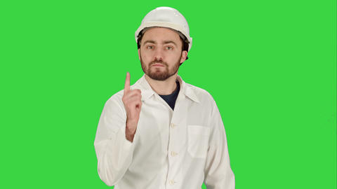 Man in the construction helmet with a raised finger on a Green Screen, Chroma Footage