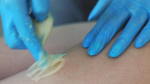 Close-up of the hand of the master of hair removal remove small hairs with a Live Action
