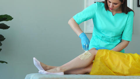 The girl talks on the phone and smiles during hair removal on the legs in the Live Action