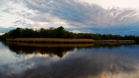 Storm clouds moving in over the lake at sunset. Colorful sky of blue, yellow and Footage