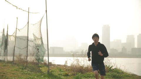 Healthy young Japanese runner running along tail near the water overlooking Osak Footage