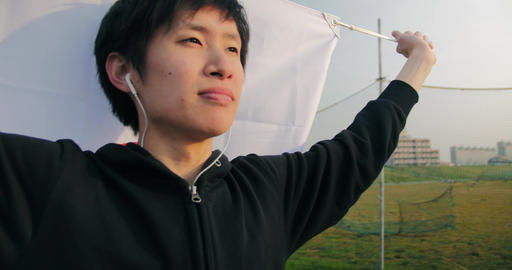 Inspirational young Japanese man holds his nations flag while running looking ov Footage