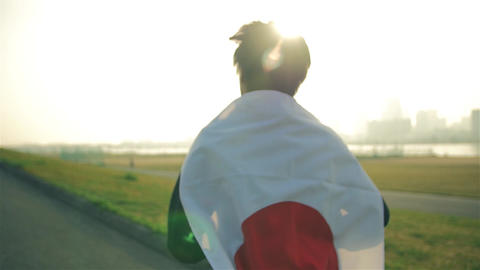 Inspiring Japanese runner runs holding his Japanese national Flag training Footage