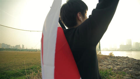 Inspiring Yuong Japanese man holds his flag high after running feeling proud Footage