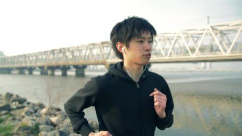 Japanese male runner trains in near the river in Osaka Japan Streadycam shot ビデオ