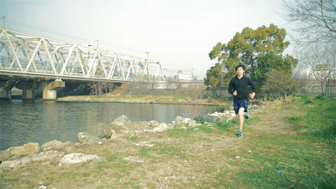 Young Japanese Fitness runner runs near water in local park Osaka Japan Footage