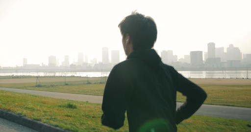 Young Japanese man runs up the hill and celebrates looking over city and river 4 Footage