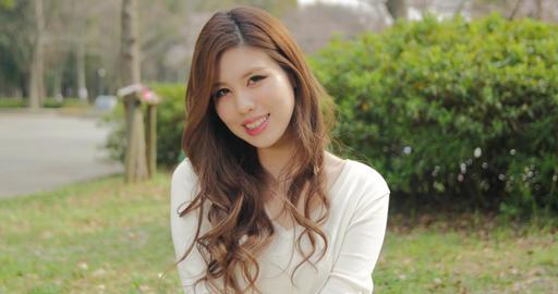 Attractive Japanese girl wearing white smiles for the camera sliding shot ビデオ