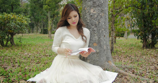 Beautiful Japanese girl reads book and laughs under green trees at the park 4K Footage
