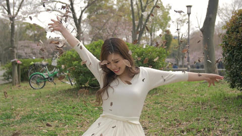 Beautiful Japanese girl sitting on the grass throwing leafs in the air Slow moti Footage