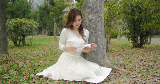 Beautiful Japanese young women reads under a tree and smiles sliding wide shot 4 ライブ動画