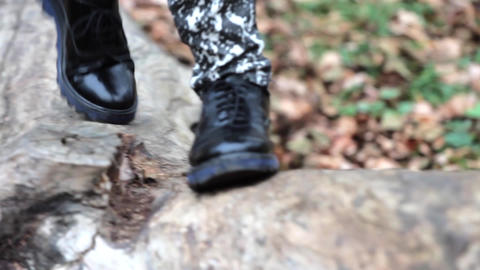 Feet shod with black shoes of a man passing over a brook, over logs down to the  Footage