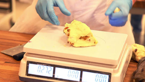 Dough is weighed on a scale at the bakery Footage