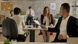 Business people of mixed ethnicity working in office, black man giving to asian Footage