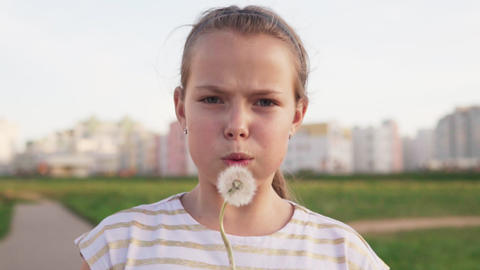 Cute little girl blowing on dandelion and smiling on urban lawn Footage