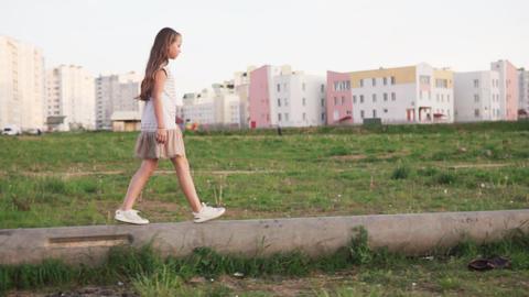Little girl walking on concrete log on urban wasteland Footage