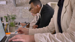 Business team of mixed ethnicity working in modern office, writing on paper Footage