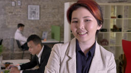 Young business asian woman looking in camera in modern office, smiling, black Footage