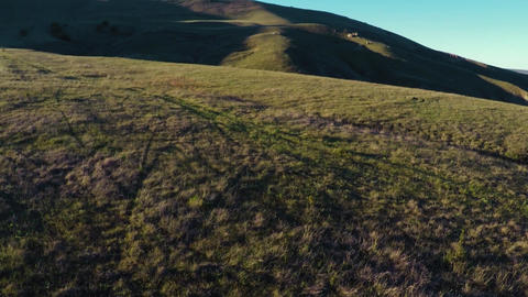 Drone aerial flight above valley with hills at evening Sun rays on horizon Footage