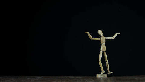 Stopmotion wooden figure dummy in studio on black background rotating and Live Action