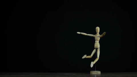 Stopmotion falling wooden figure dummy in studio on black background rotating Live Action