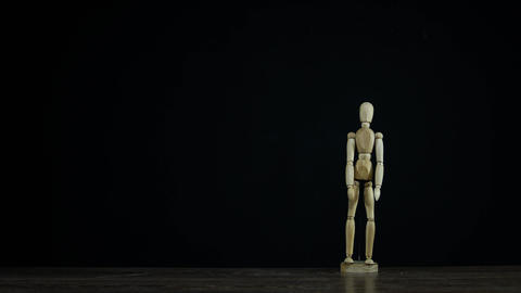 Stopmotion wooden figure dummy applauds in studio on black background for titles Live Action