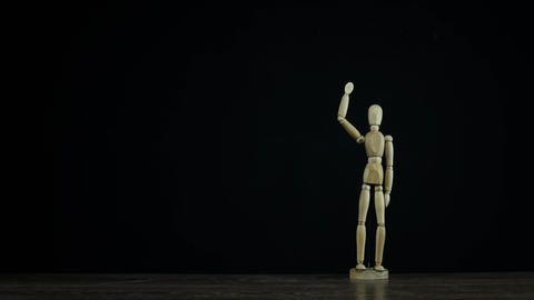 Stopmotion wooden figure dummy in studio on black background Live Action