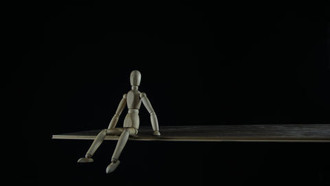 Stopmotion wooden figure dummy procrastinates in studio on black background Live Action