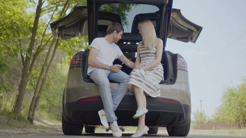 Happy in love couple sit inside th trunk of the car and talking, first date Live Action