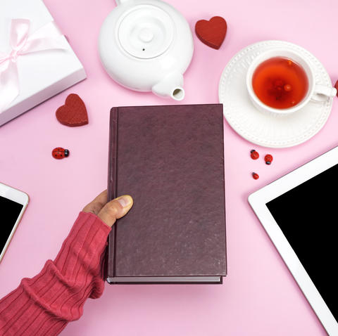 female human hand holds a book in a brown cover Photo