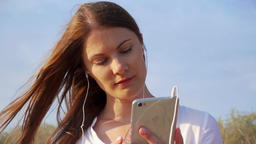 Young happy woman using mobile against blue sky. Female listening music via Footage