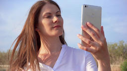Woman using mobile against blue sky. Smiling female taking selfie photo on Footage