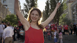 Young pretty woman cheering and jumping on street during festival, smiling Footage