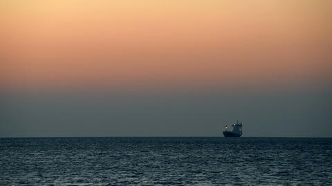 Ship anchored offshore at sunset Footage