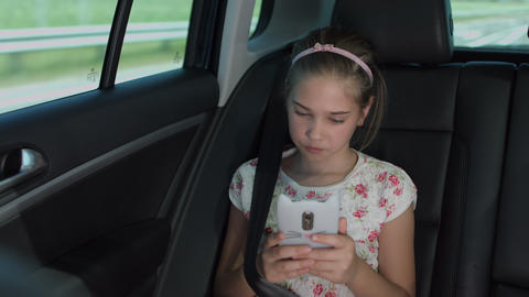 Little girl text messaging on smart phone in car Footage