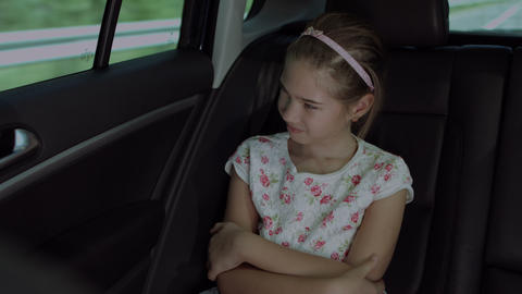 Cheerful girl riding in the back seat of the car Footage